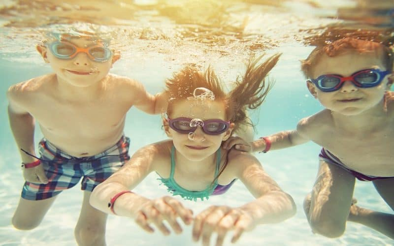 Three kids swimming underwater. Little girl and her brothers having fun in the swimming pool. Focus in the little girl, brothers are out of focus.