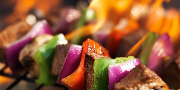 Steak shish kabobs on grill with flames
