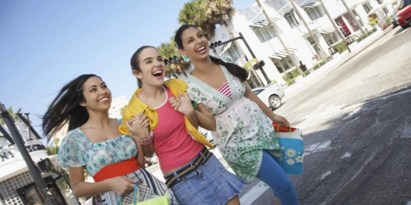 Cheerful teenage girls with shopping bags crossing street
