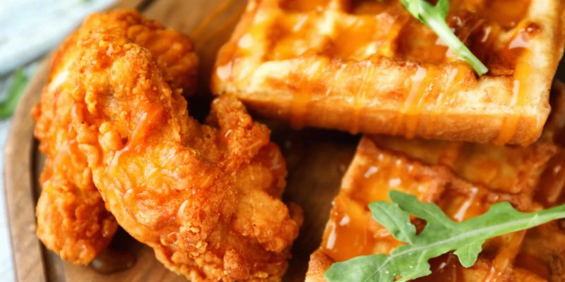 Delicious waffles with chicken and honey on wooden board